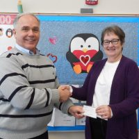 Kim Tate of the Shelby Optimist Club presents a $1,000 check to Hesperia Community Library Director Kay Brennan.